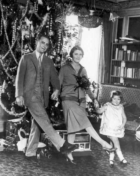 1925: American author F Scott Fitzgerald (1896 – 1940) dances with his wife Zelda Fitzgerald (nee Sayre) (1900 – 1948) and daughter Frances (aka 'Scottie') in front of the Christmas tree in Paris.