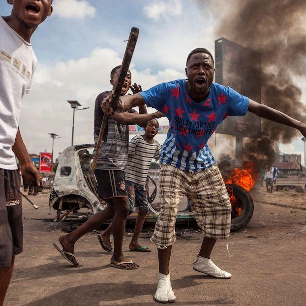 Manifestanti davanti a un'automobile che brucia durante una protesta per chiedere le dimissioni del presidente Joseph Kabila, che è in carica dal 2001