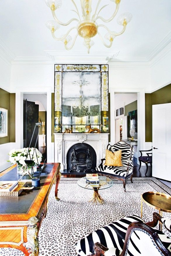 Maximalist Australian living room with animal print armchairs, gold chandelier, and antique mirror above fireplace