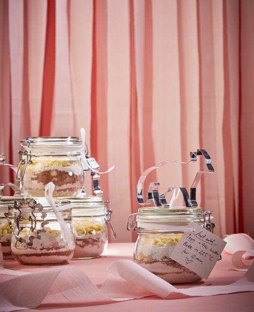 Ingredienser til kagedej ligger lagvis i glas med en håndskrevet besked og kageform bundet fast til låget.