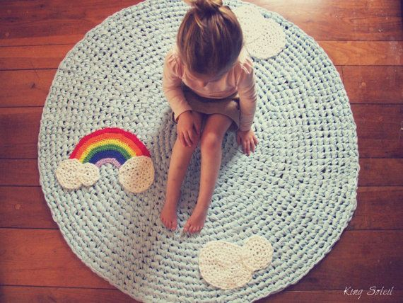 A soft crocheted rug with clouds and a rainbow is just the place for daydreaming.