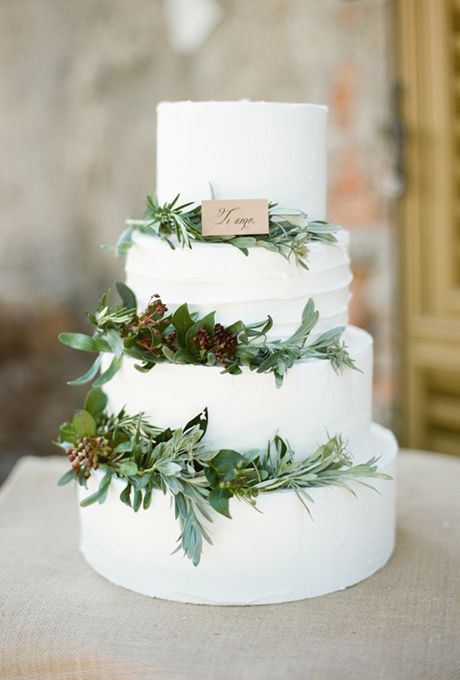 Four-Tiered Wedding Cake Decorated with Greenery. A traditional wedding cake goes country-chic with rustic greenery.