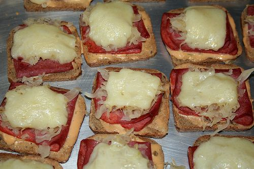 Open Face Cocktail Reuben-ettes: Butter or margarine, Party rye bread  Cooked corned beef, sliced thin, Swiss cheese, sliced thin, Jar of sauerkraut, well drained & chopped, 1000 Island dressing *Seal bread by spreading a thin layer of butter on one side. Place a dollop of dressing on the butter & spread to cover. Tear the corned beef in pieces & place on top of the dressing followed with the sauerkraut. Top with the Swiss cheese. Bake in a 375 oven until cheese melts. Serve warm.