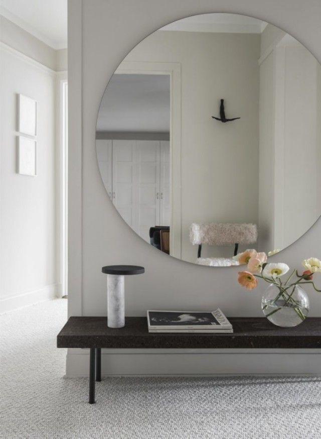 Stor rund spegel och ljusgrå vägg