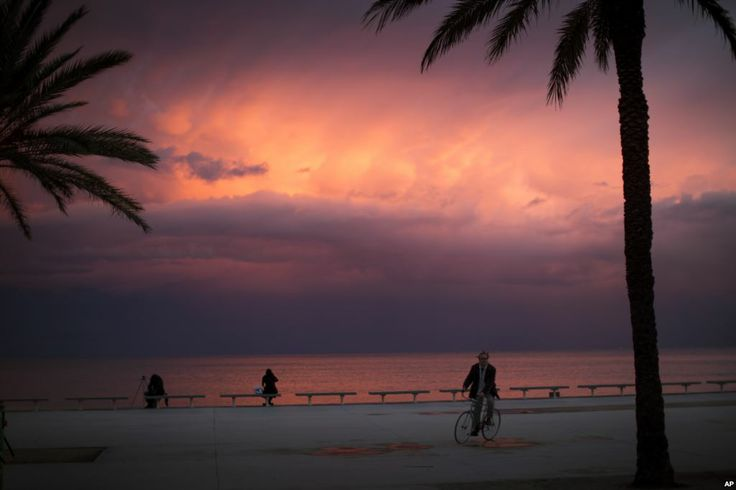 Seorang pria mengendarai sepeda ketika matahari tenggelam di pantai Mediterania Barcelona, Spanyol, 10 Februari 2014.
