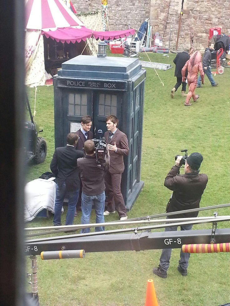"""via RadioTimes: """"One photograph shows the tenth and eleventh Doctors being interviewed outside the Tardis, while in the background a Zygon strides purposefully away (©@HWB Cymru)."""""""