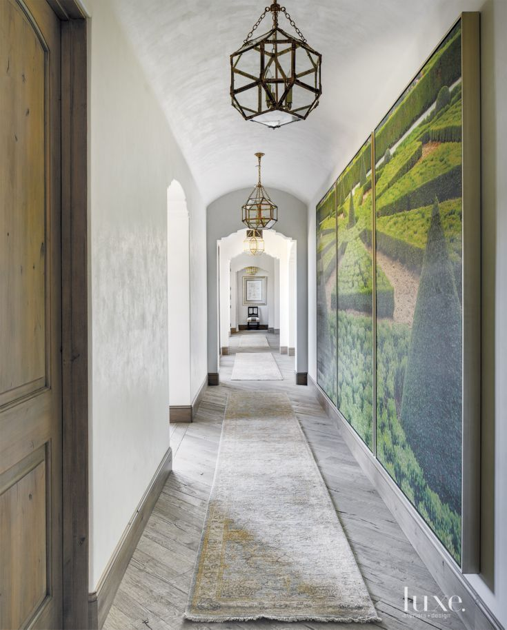Charlotte Moss' French garden triptych from Century Furniture dresses a wall in the main hallway. Visual Comfort fixtures from Valley Light Gallery cast a glow on plaster-finished walls that designer and homeowner Kim Scodro calls a balance of cream and gray.