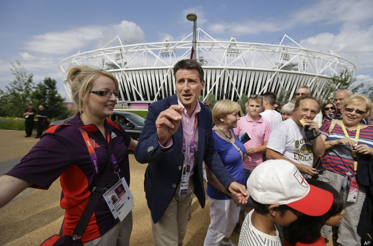 Sebastian Coe, Chair of the London 2012 Organizing Committee, center, greets members of the public outside the Olympic Stadium in the Olympic Park at the 2012 Summer Olympics, Saturday, July 28, 2012, in London.