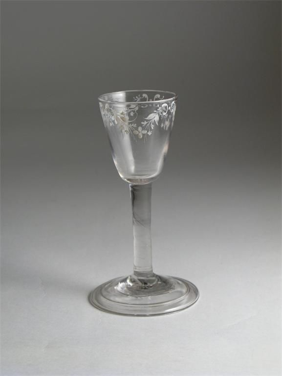 A rare Beilby enamelled wine glass c.1765, decorated in white with four floral garlands, probably by Mary Beilby, raised on a plain stem above a folded foot, 14cm. Cf. J. Rush, A Beilby Odyssey, p.60, pl.18 for a glass with the same design raised on an opaque twist stem. It is extremely unusual to find a Beilby glass raised on a plain stem.