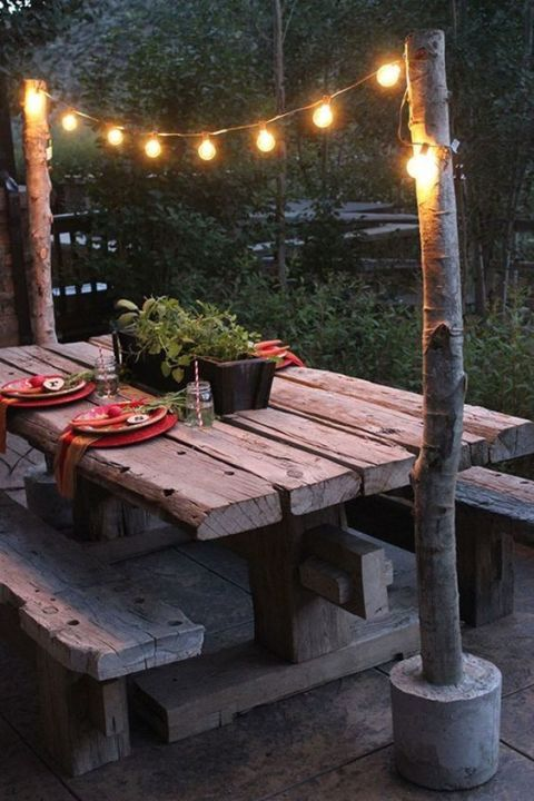 Make these DIY string light poles to create a simple overhang for your backyard picnic table. Click through for more backyard string light ideas.