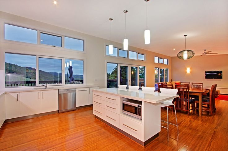 This Kitchen and Dining room from this Luxury Contemporary Weatherboard home is truly divine. The long vertical windows open up to a stunning mountain view that can only be achieved building on a Sloping block.