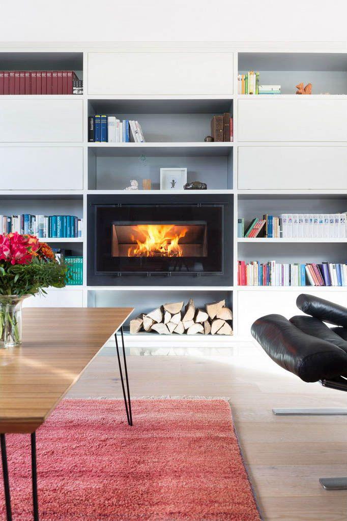 Die einseitige Kaminfeuerung mit nach oben klappbarer Scheibe ist komplett in einem Bücherregal eingelassen.
