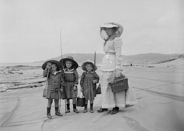 Woman and children on beach in Lorne, Ca., 1900