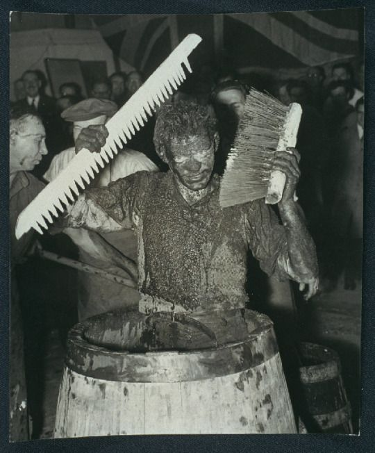 Cooper (barrelmaker) Robert Leece, is pictured in a barrel that he made himself, whilst covered in soot, ash and water.  This is all part of an initiation ceremony to mark his graduation from apprentice to full-fledged cooper, practiced since the days of Queen Elizabeth I. Stag Brewery, Pimlico, London, 1955.