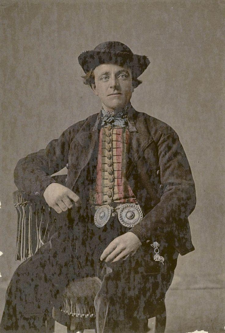 Man in streekdracht uit Nieuw- en St. Joosland, circa 1880. De man draagt onder zijn jas een meerkleurige hemdrok, gesloten door een rij zilveren knopen. Om zijn hals draagt hij een halsdoek, waarboven de gouden keelknoop zichtbaar is. De broek word middenvoor gesloten door grote zilveren 'broekstukken'. Op het rechter dijbeen hangt de zilveren chatelaine van het horloge. #Zeeland #NieuwStJoosland
