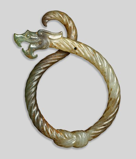 3rd C. BCE. Jade Serpentine Dragon Pendant, this pendant makes hard jade appear impossibly supple and pliant as a twisted rope knotted at the bottom. Eastern Zhou dynasty (770–256 BCE) China.