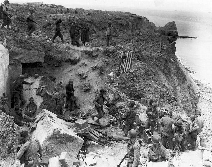 Quelques Rangers américains après la bataille. En fond, des prisonniers partant en captivité. Pointe du Hoc, Normandie, 8 juin 1944