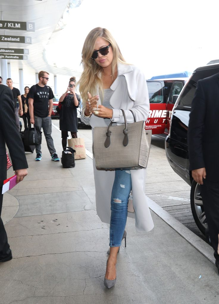 At the airport, Khloé paired a sophisticated white coat and structured bag with ripped jeans.