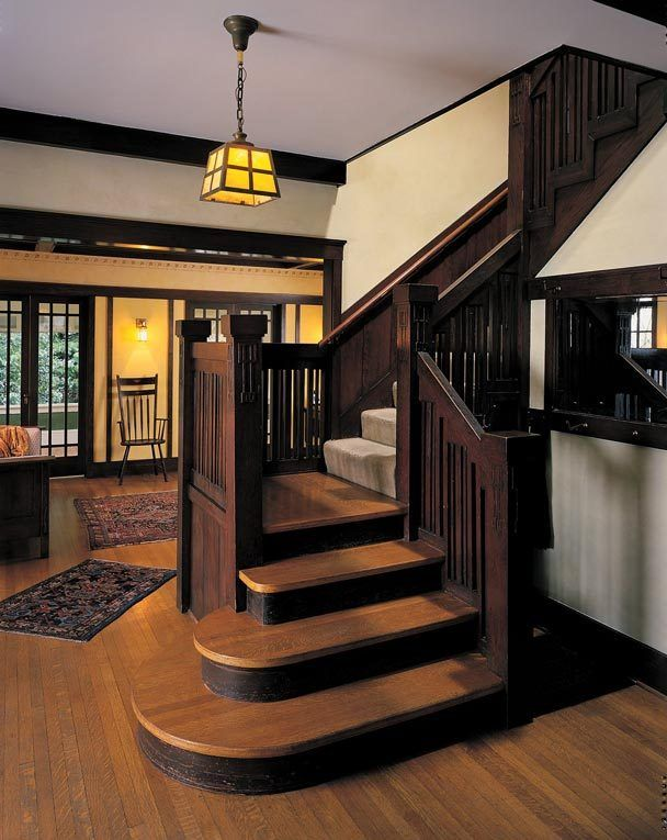 The entrance hall of Doug and Joan Stewarts' 1909 Craftsman home in the Montlake neighborhood has a handsome vertical-slat stairway and newel posts with pendent-motif raised patterns that are tied to similar patterns centered on the dining room and living room pediments.