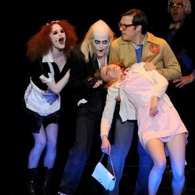 "Actors on stage reenacting a scene from the ""Rocky Horror Picture Show."""