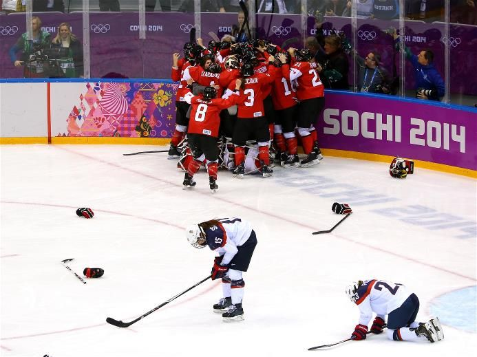 Marie-Philip Poulin (#29) of Canada celebrates with teammates after scoring the game-winning goal against the United States in overtime, as Anne Schleper (#15) and Michelle Picard (#23) of the United States react, during the Ice Hockey Women's Gold Medal Game. Sochi 2014 - Best of Day 14.