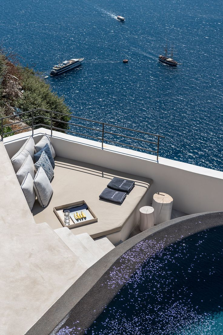 Roof terrace and black infinity pool, part of the luxury boutique hotel in Santorini - aboratorium renovate seven suites at Porto Fira luxury hotel in Santorini, Greece. Luxury hotel designs feature on the www.martynwhitedesigns.com interior design blog.