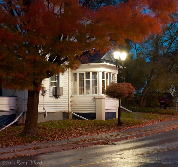 Old white house in the fall with a red maple tree and glowing street lights.