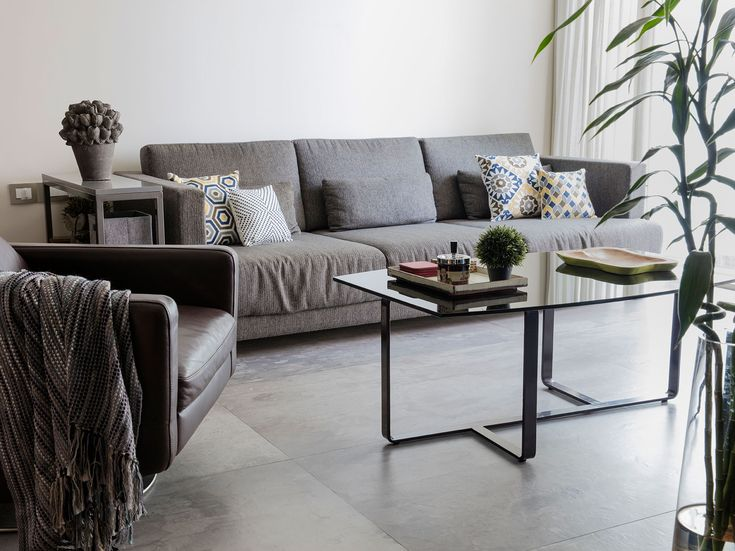 The Living Room Is Done Up In Shades Of Grey And Has Bare Walls To Create