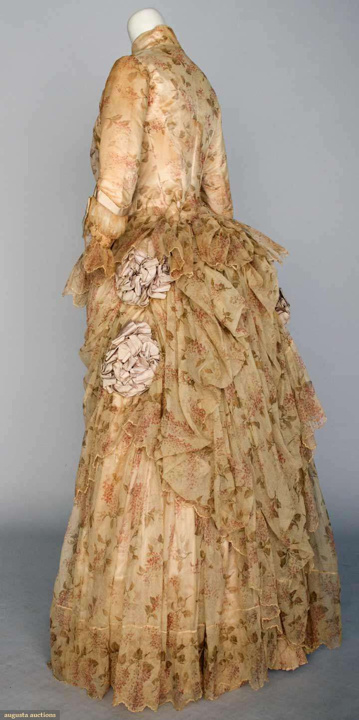 """PRINTED TULLE BUSTLE DRESS, NYC, 1886  April 17, 2013 - NEW YORK CITY  2-piece cream cotton tulle printed w/ small sprays of rose colored flowers & green leaves, a-symmetrically draped skirt w/ ribbon rosettes, petersham label """"C. Donovan 216 5th Ave. N.Y."""", B 32"""", W 22"""", Skirt L 41""""-46"""", (silk lining stained, shows through the tulle) fair"""