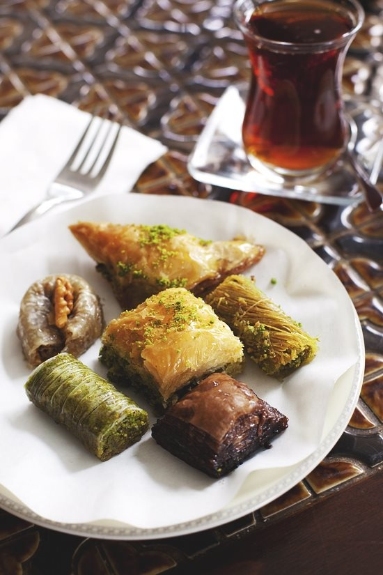 Tea and Baklava:  In Iran, a drier version of baklava is baked and presented in smaller diamond-shaped cuts flavored with rose water. The cities of Yazd and Qazvin are famous for their baklava, which is widely distributed in Iran.Persian baklava uses a combination of chopped almonds and pistachios spiced with cardamom and a rose water-scented syrup and is lighter than Middle Eastern versions.