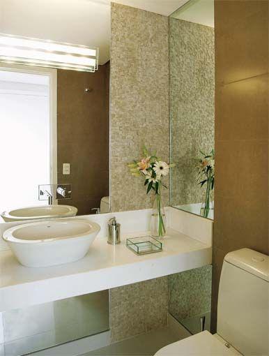 Uma parede de mosaico e o suave degradê em tons de bege valorizam este lavabo. Atrás do vaso, um elegante porcelanato com textura de couro. Projeto de Flávia Portela.