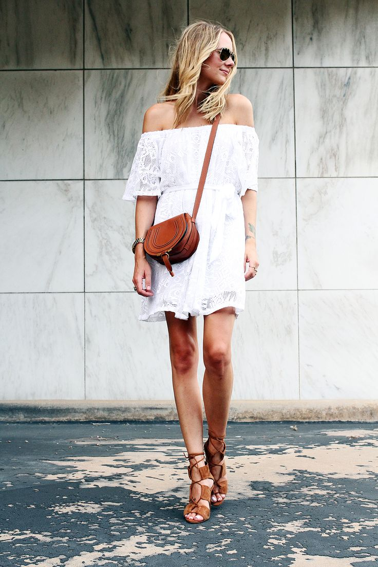 Off the shoulder white dress with cognac colored leather accessories