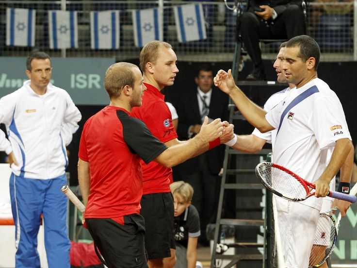 Belgians Olivier Rochus (L) and Steve Darcis 2nd L) congratulate Israelis Jonathan Erlich (2nd R) and Andy Ram (R) after Israel won the doub...