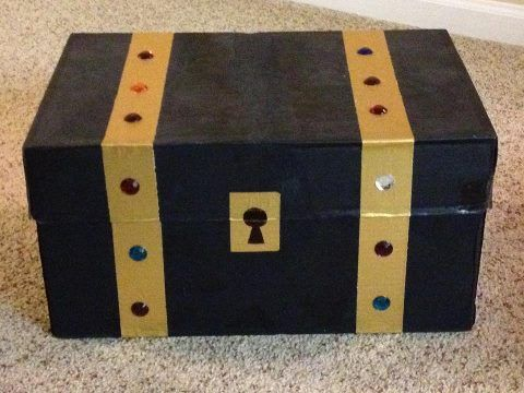 """Treasure Chest."" A copy paper box that's painted black, with gold duct tape and craft jewels."