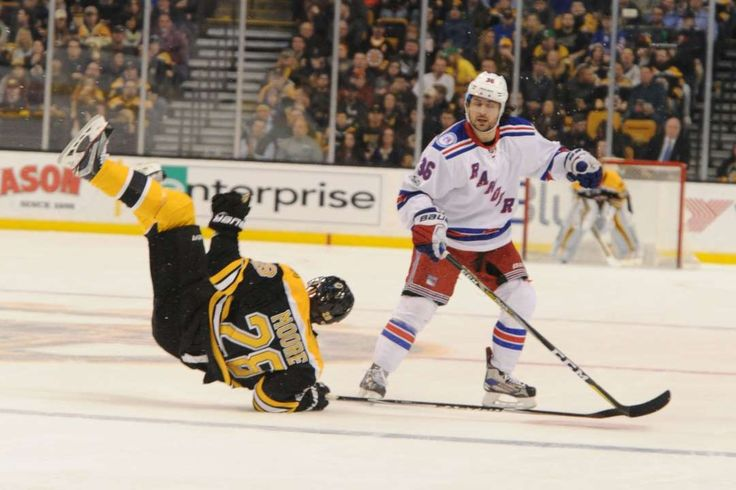 Falling hard:    Dominic Moore of the Boston Bruins falls on the ice during a play against Mats Zuccarello of the New York Rangers at the TD Garden on  March 2 in Boston. New York won 2‐1