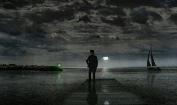 Une fois arrivé chez moi, j'aperçus un homme sur le quai de mon voisin. Et quelque chose me donna a pensé que c'était Mister Gatsby. Il paraissait tendre les bras vers l'eau ténébreuse en un geste curieux... La lumière verte ! [...]