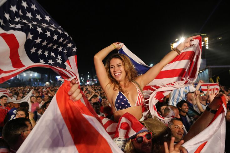 Fans of the U.S. national soccer team celebrate their team's victory during a live broadcast of the soccer World Cup match between the Unites States and Ghana, inside the FIFA Fan Fest area on Copacabana beach, Rio de Janeiro, Brazil, Monday, June 16