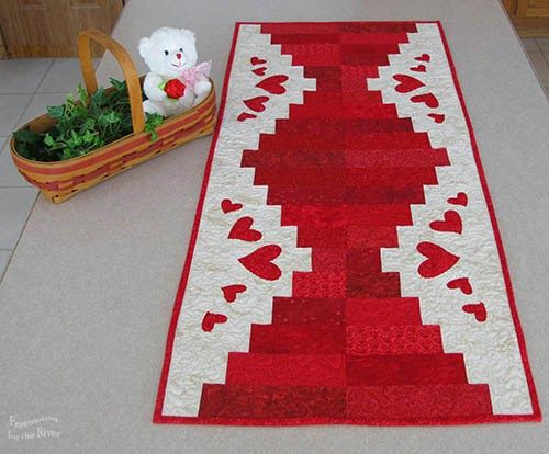 "Red and White Table Runner by Connie...My project is a little different because I actually designed it first in my head, then graph paper and finally in Electric Quilt 7.  I knew I wanted to make a table runner using a cute little bundle of red 2 1/2"" strips...I knew I was going to do some appliqué on the block...table runner is an odd size.....finished it is 18 x 42"