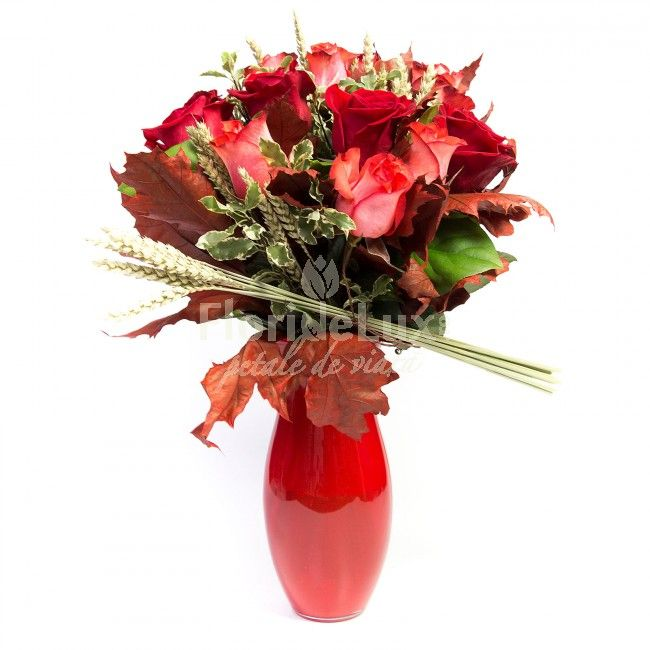 bouquets from red and orange roses, decorated with autumn leaves and delivered in this red glass vase.