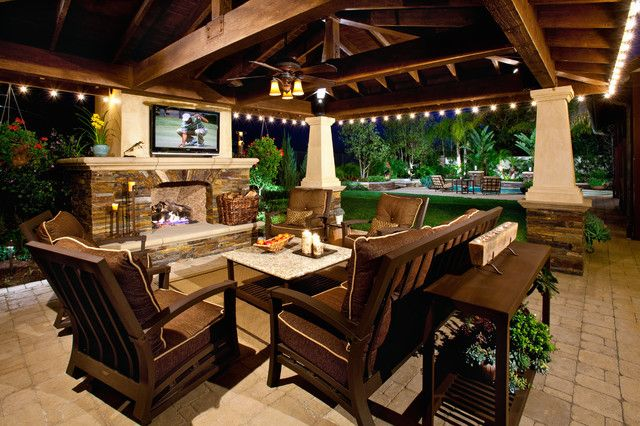 Outdoor covered patio with fireplace and TV above
