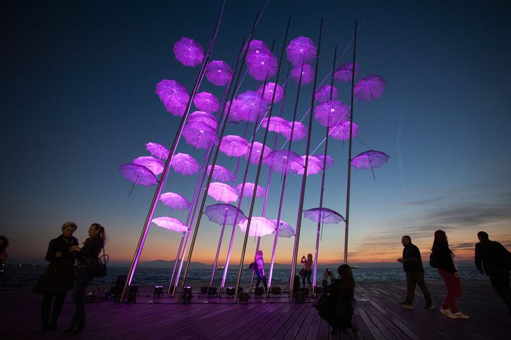 "People stand around ""Umbrellas"", the sculpture by Giorgos Zogolopoulos, as it is illuminated in pink light to mark the Breast Cancer Awareness Month in Thessaloniki in northern Greece, Oct. 21, 2014."