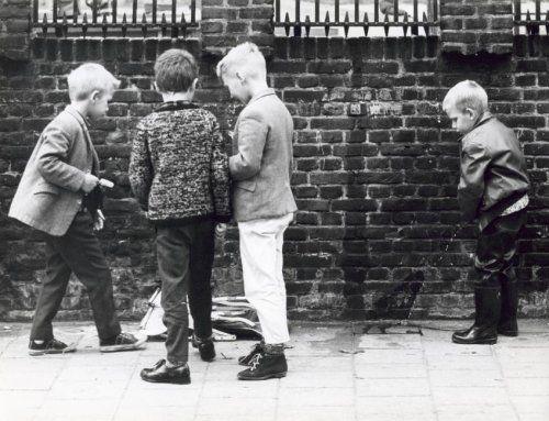 Wildplassers: Schooljongen met laarzen plast in het bijzijn van andere jongens, Nederland, jaren '60.