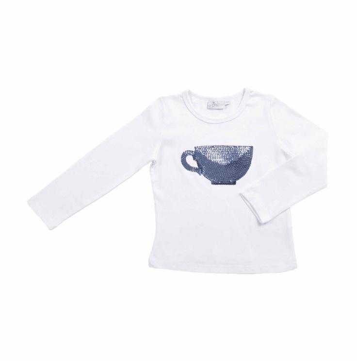 Franela blanca de algodón para niña con cuello redondo y mangas largas. Al frente, como adorno, tiene una taza bordada en lentejuelas azul brillante.
