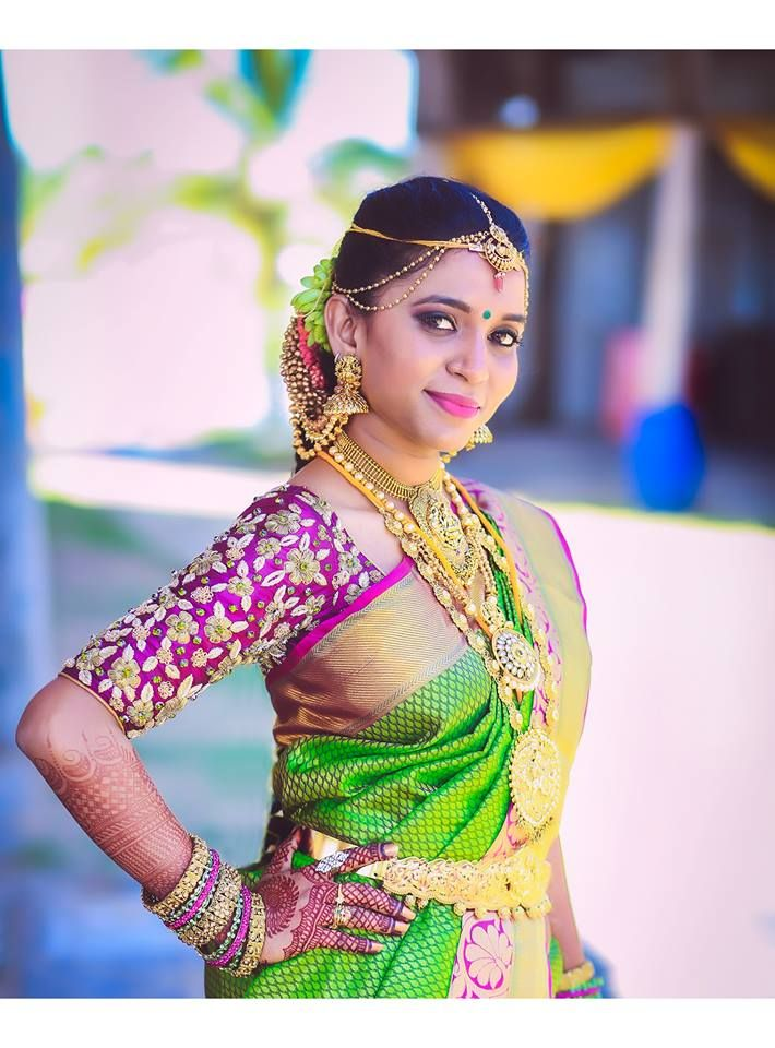 South Indian bride. Gold Indian bridal jewelry.Temple jewelry. Jhumkis.Green silk kanchipuram sari with contrast embroidered purple blouse.Braid with fresh flowers. Tamil bride. Telugu bride. Kannada bride. Hindu bride. Malayalee bride.Kerala bride.South Indian wedding.