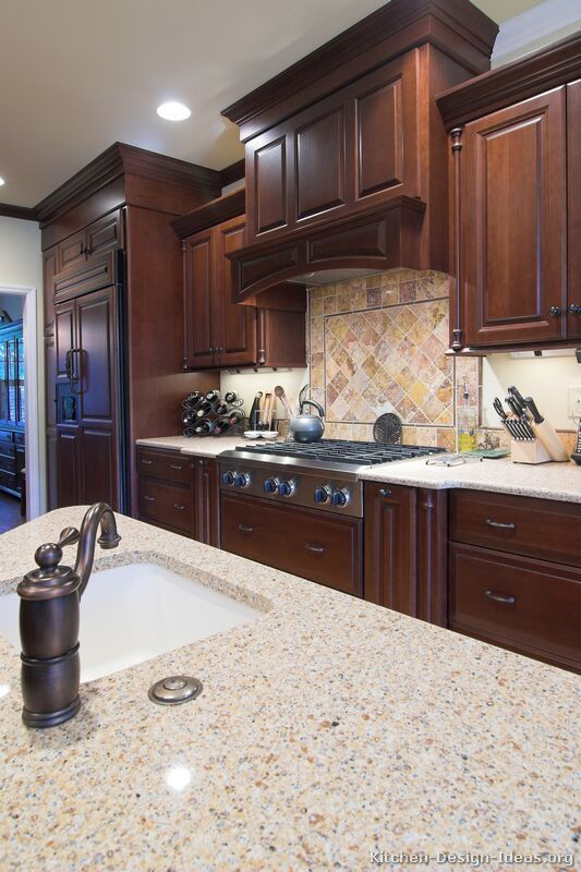 #Kitchen of the Day: Dark cherry cabinets, matching refrigerator panels, a decorative wood hood, and a simple tile backsplash. Kitchen # 3 in Traditional Dark Cherry Kitchens