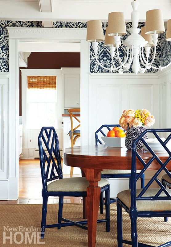 Navy lacquered chairs with linen fabric, wood table, white walls with navy patterned wallpaper, textured rug.
