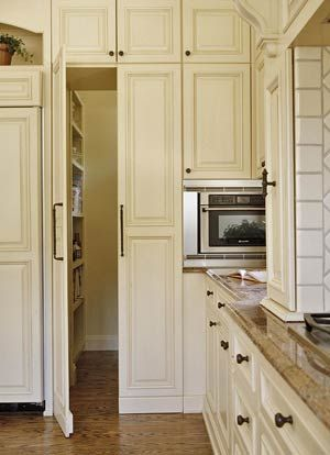 """""""While panels alongside the refrigerator blend in with surrounding cabinets, they are actually doors opening to a hidden walk-in pantry."""""""