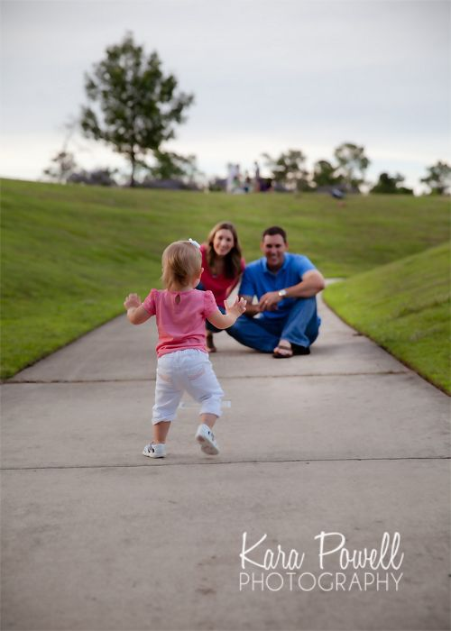 Magnolia, TX one year old running into her parent's arms at the park, taken by Kara Powell Photography.