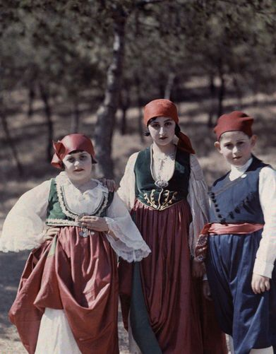 Girls and boy wear Cretan costumes at pageant in the ancient stadium- Athens. National Geographic's Greece in Color from the 1920s Photographer: Maynard Owen Williams in the 1920s
