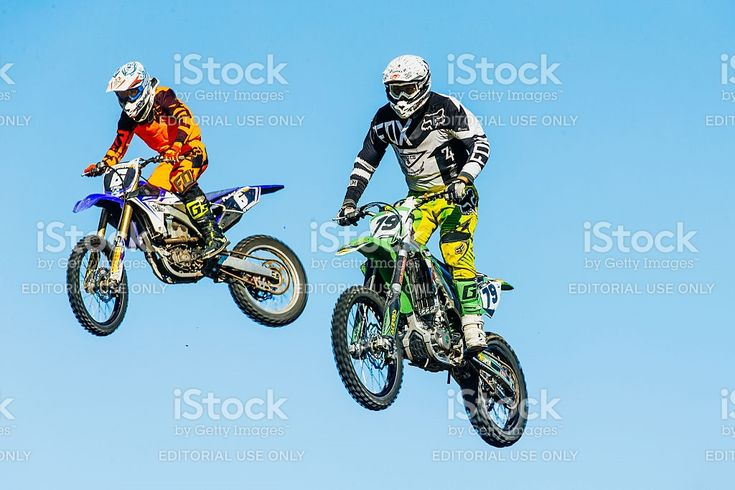 Miasskoe, Russia - May 02, 2016: closeup of two motorcyclists jump from a mountain on background of blue sky during Cup of Urals motocross